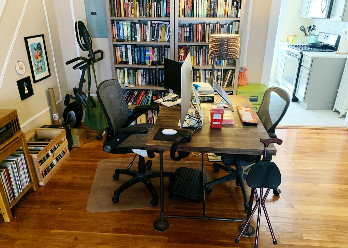 Dining table set up as a desk with a cane, stool, and medical supplies visible in addition to computer screen, bookshelves, records, and desk chair.