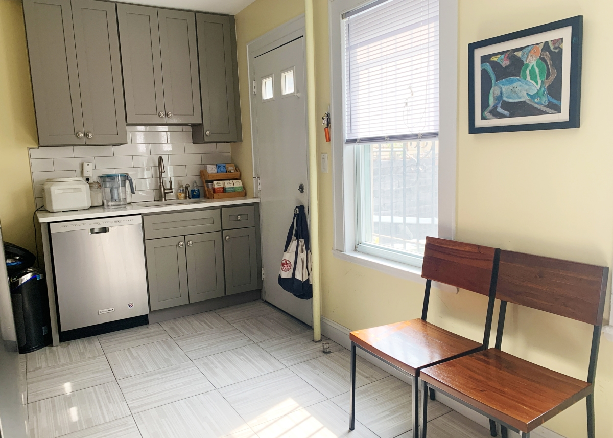 Kitchen with two dining chairs tucked against the right wall, cabinets and dishwasher visible as well as window with sun streaming through onto the floor.