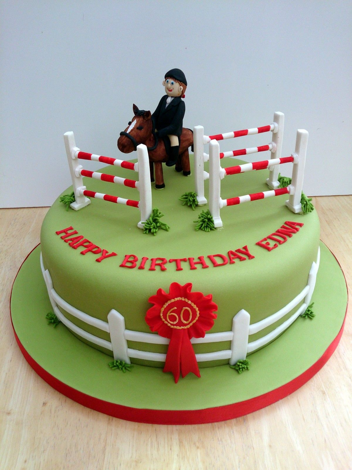 a cake saying happy birthday edna with a woman on a horse and some fences