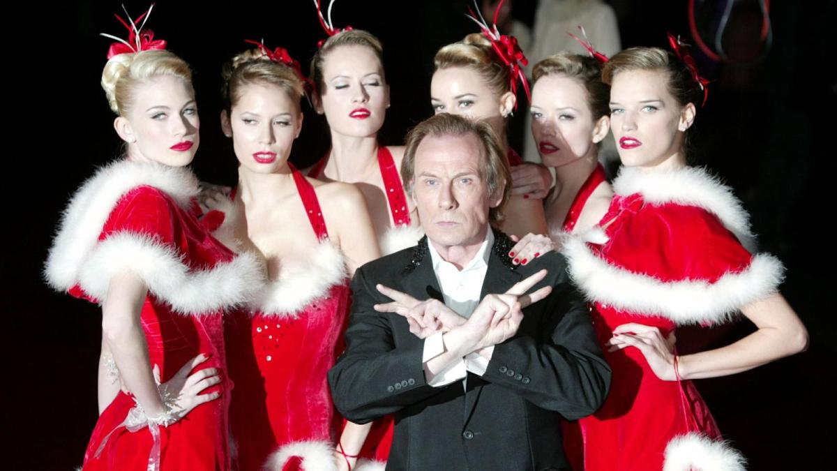 """still from """"Love Actually"""" with a bunch of girls in sexy Santa outfits"""