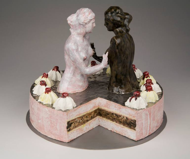 a sculpture of a cake that looks like a sculpture of two women groping each others