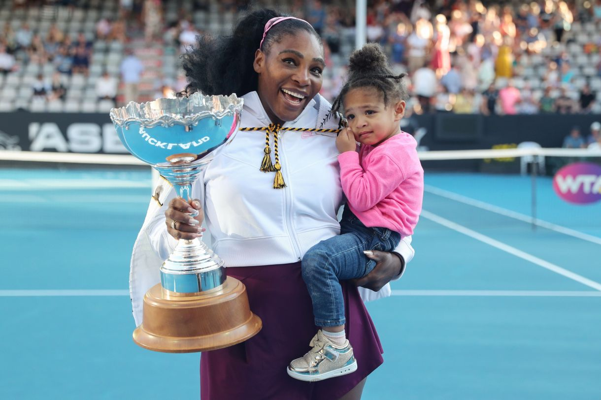 Serena Williams, the greatest athlete of all time, holding a trophy in one hand and her daughter in the other