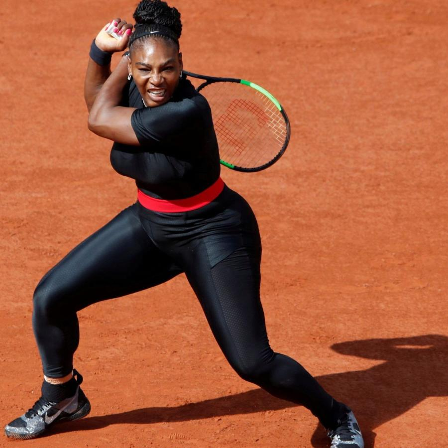 Serena Williams, the greatest athlete of all time, in a black catsuit after returning a shot on the red clay of the French Open
