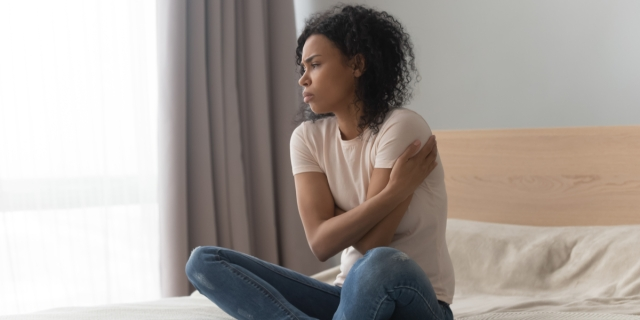 Black woman with curly medium length hair sits on a bed, wearing jeans and a white tee, hugging herself with her crossed arms, looking away from the camera as though in thought.
