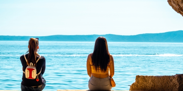 Two women sit far apart together on a beach