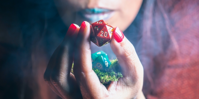 Image of a red 20 sided rpg die hold by a woman of color blowing onto it for good luck.