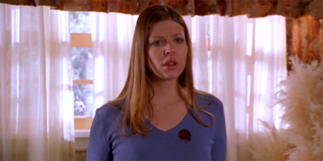 Tara Maclay of Buffy the Vampire Slayer stands in front of a window with a shocked look on her face and a bullet hole over her heart