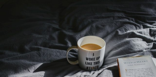 """A dramatically lit photo of a cup of coffee in a mug that reads """"I woke up like this #tired"""" nestled into rumpled bedsheets along with an open hardcover book."""