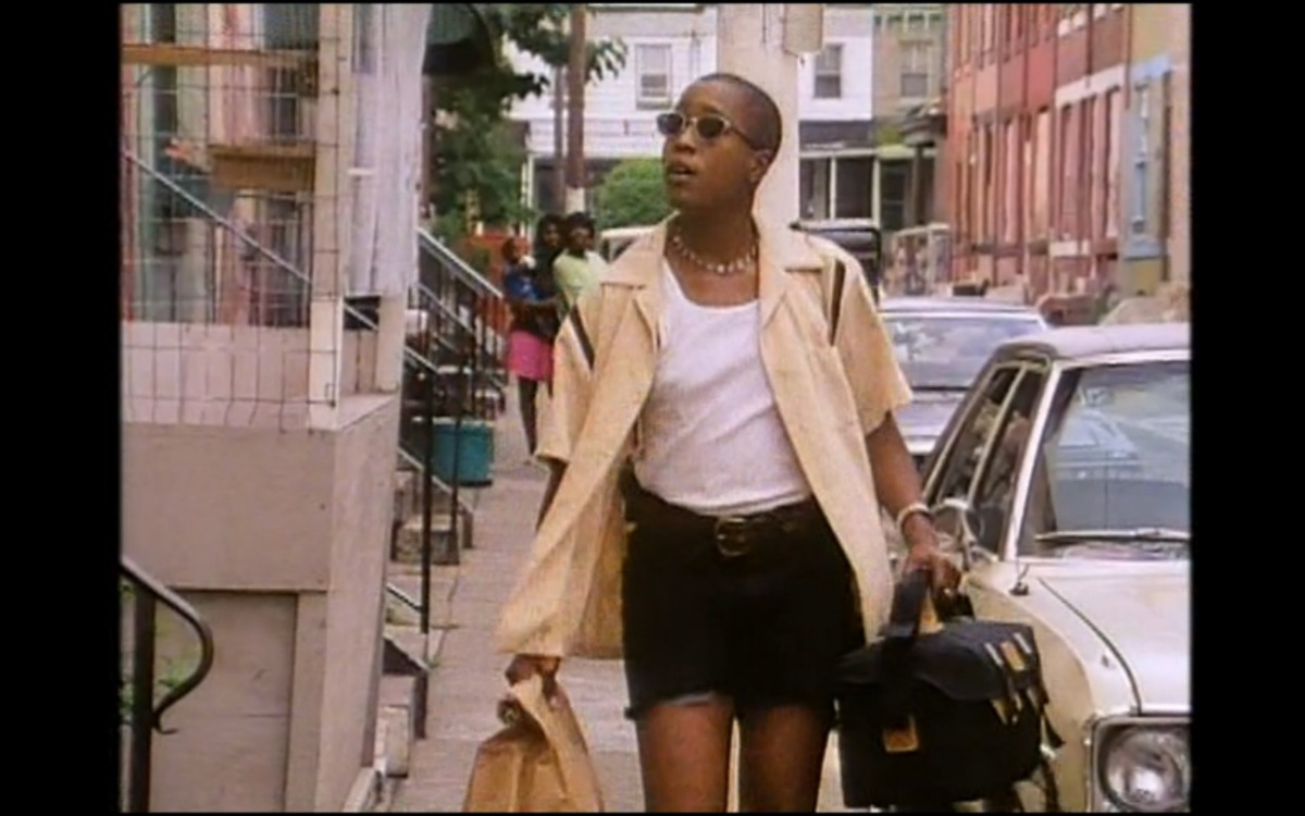Image shows a Black woman wearing a white shirt, Black shorts and a cream open shirt on top holding a bookbag walking down a nyc street in the 90's