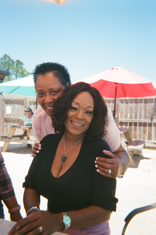 Rachel and Sheila Smallman, owners of lesbian bar Herz, pose together in a sunny outdoor location. They are both smiling.