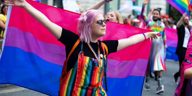 A person with shoulder length pink hair and rainbow overalls uses the bisexual pride flag as a cape during a pride march.