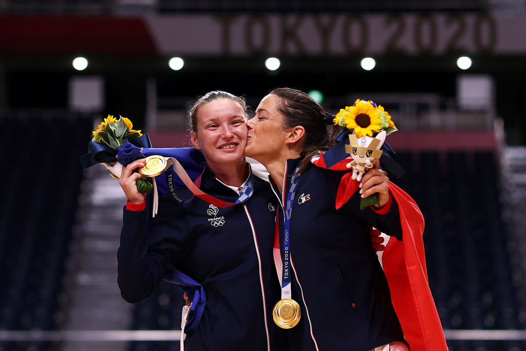 Cleopatre Darleux kisses teammate Amandine Leynaud of Team France while posing with their gold medals during the medal ceremony for Women's Handball on day sixteen of the Tokyo 2020 Olympic Games at Yoyogi National Stadium on August 08, 2021 in Tokyo, Japan. (Photo by Dean Mouhtaropoulos/Getty Images)