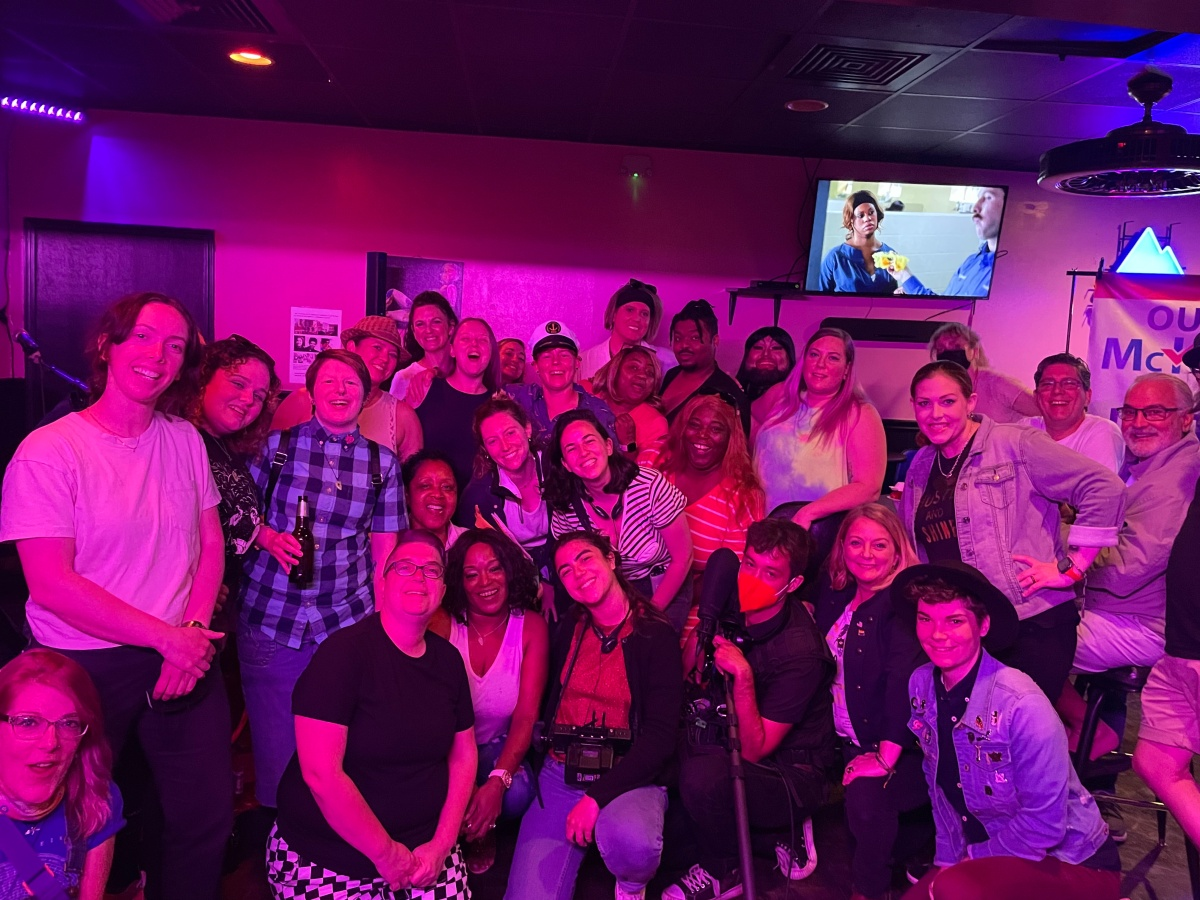 A huge group gathers at Herz, a lesbian owned bar in Mobile, Alabama. Everyone is smiling and looks happy.