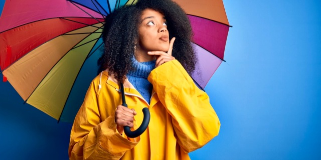 A black woman with curly hair has an inquisitive looks off to the right while pondering what does the word sapphic mean underneath a rainbow umbrella.