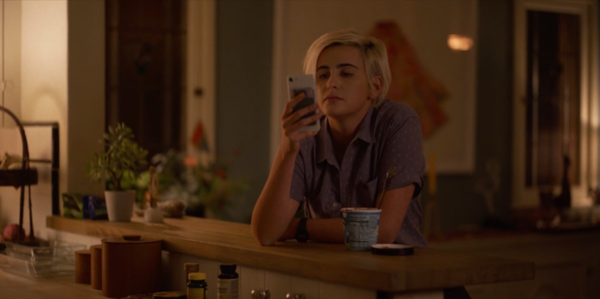 Finley sitting at the kitchen table with her phone