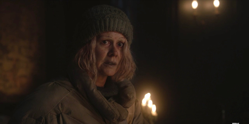 Sarah Paulson as TB Karen wearing an old beanie and big coat looks scared.