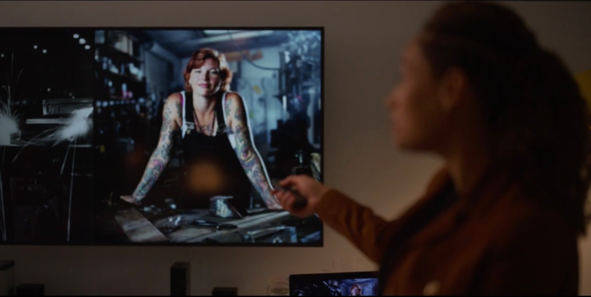 Sophie showing a slide of a girl with red hair and tattoos in workshop