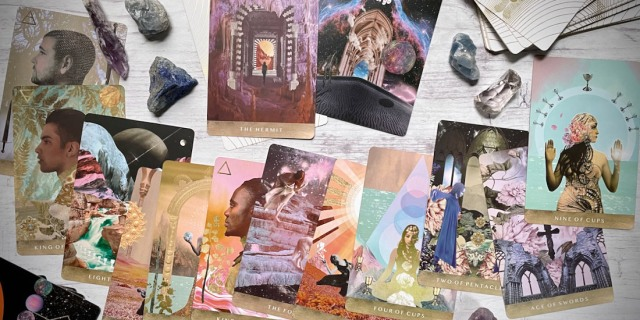 Cards from the Moonchild Tarot spread out on a white background, with the Hermit and crystals pulled forward.