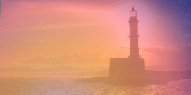 The image of a lighthouse with a color gradient of orange to purple on it.