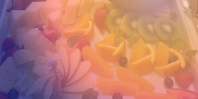 A photo of a fruit platter with a purple to orange gradient on it.