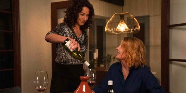 In a screenshot from the first season of The L Word: Generation Q, Bette pours Tina a glass of wine