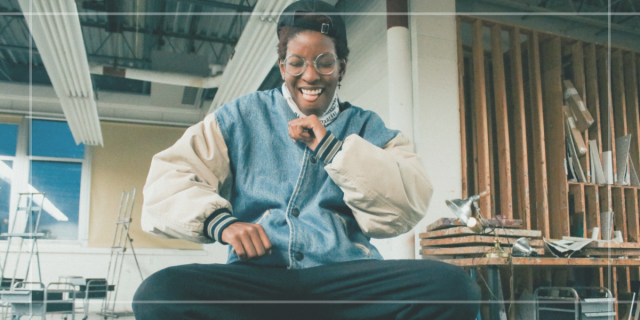Stud Lesbian — Image shows a Black person with a joyful smile mid dance wearing a oversized vintage denim jacket, a backwards hat, round glasses and black pants. They are sitting down and again, joyfully mid dance.