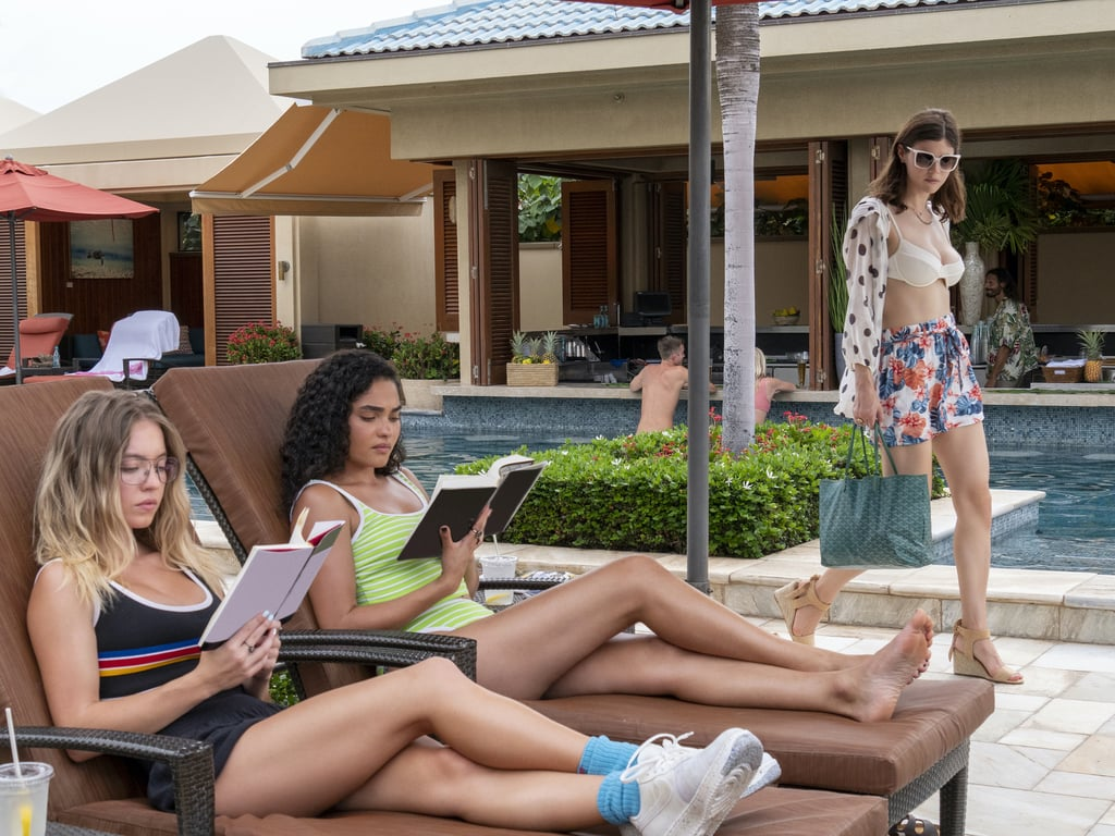 Oliva and Paula read in lounge chairs by the pool as hotel guest Rachel walks by