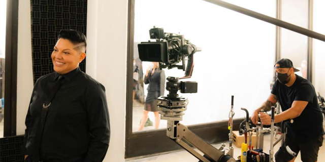 Sara Ramirez smiling in a black suit with a camera person behind her on the set of Sex and the City