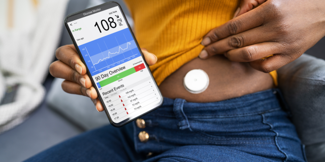 A Black person wearing a yellow top and jeans lifts up their shirt to reveal a Continuous Glucose Monitor in their abdomen. They hold up their phone, which shows a glucose monitoring app.
