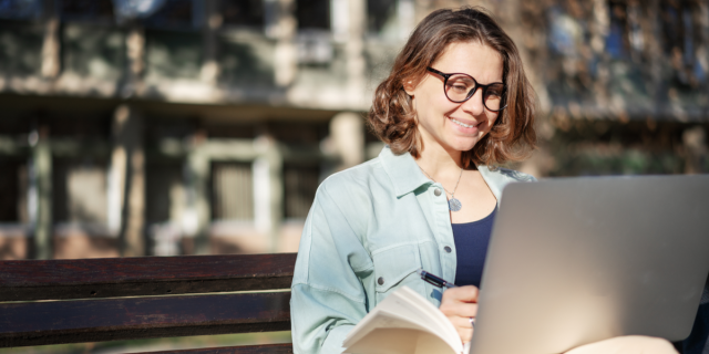An image of a white woman with glasses smiling at her computer
