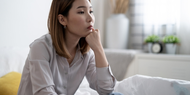 An Asian woman sits with her chin in her hands as she thinks pensively.