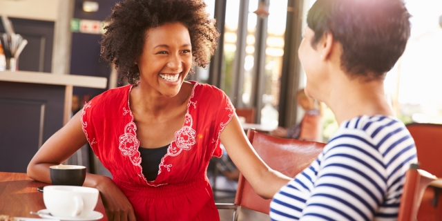 A black woman with natural hair, laughing and smiling at a friend.