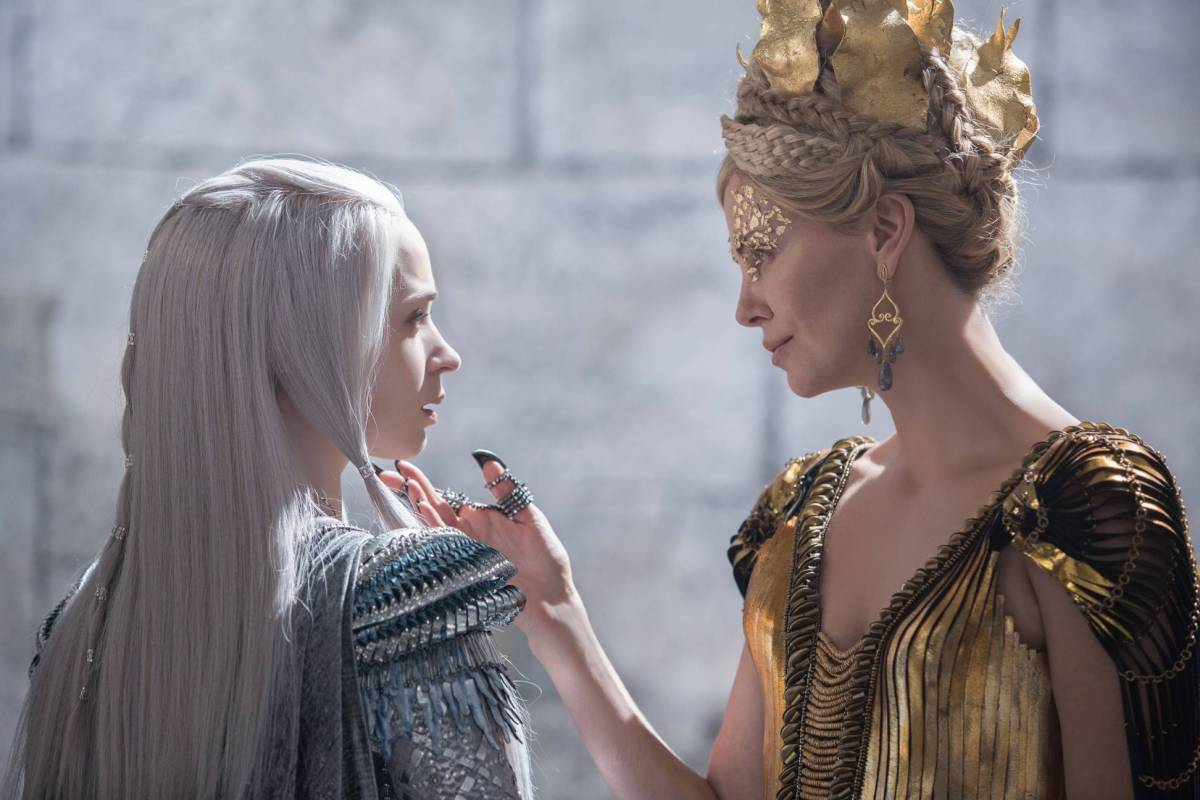 Still from The Huntsman. Charlize Theron as the evil queen strokes Emily Blunt's chin.