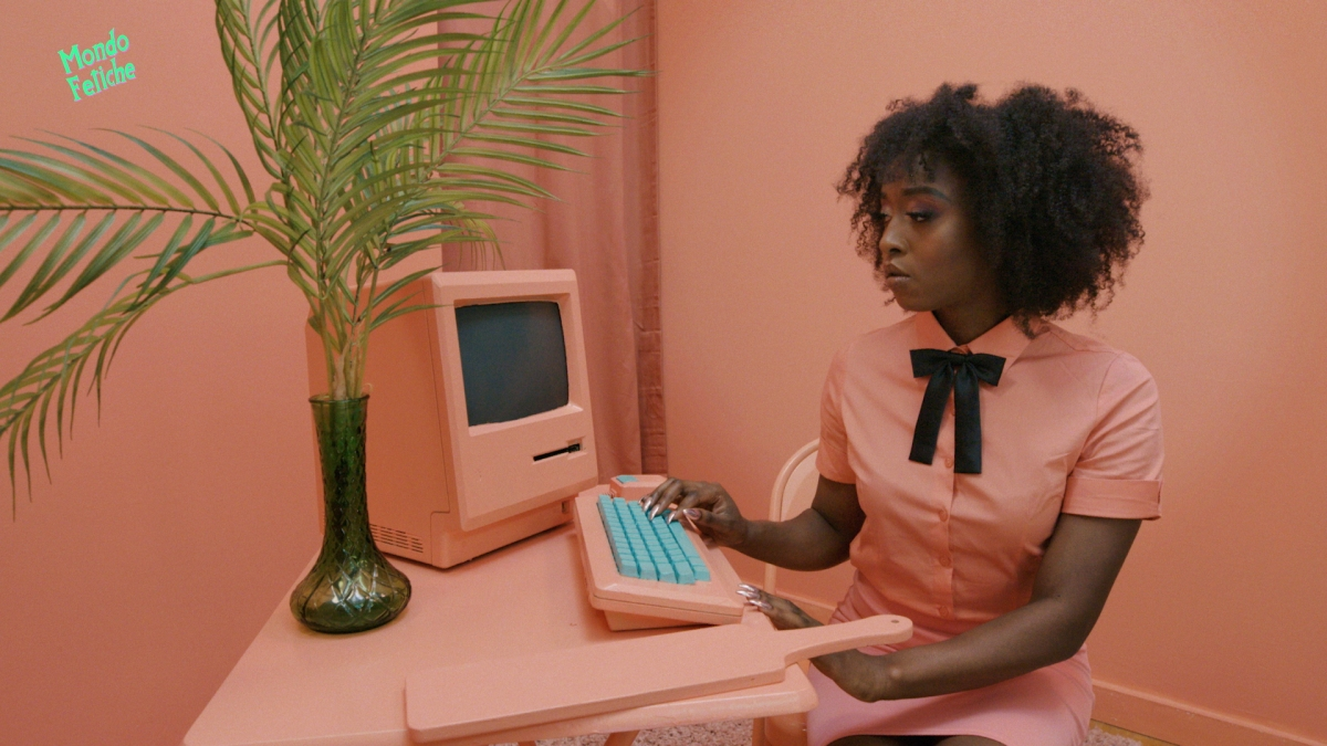 Long nails and lesbian sex: Image shows a Black woman with long nails sitting at a computer in a all peach colored room, typing at the keyboard.