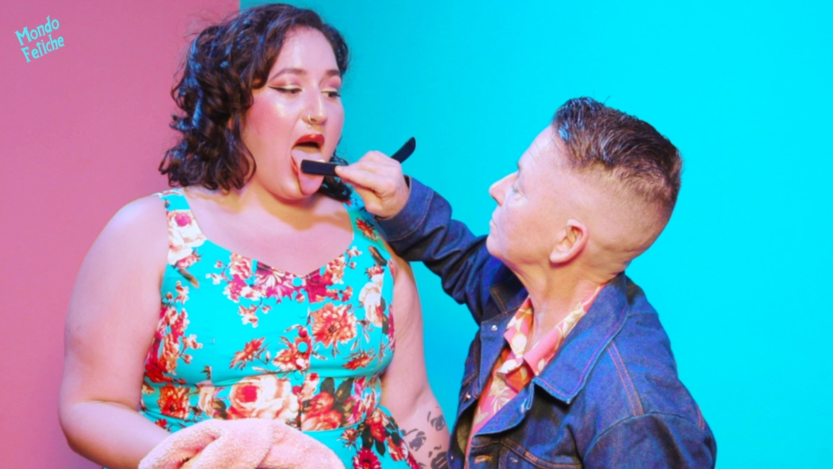 Image shows a pin-up styled person with her tongue out, while another person wearing a denim jacket puts their shaving razor on the others tongue making her lick it clean.