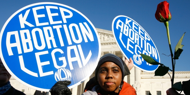 """Today is a good day to donate to an abortion fund: A black person holds a large blue sign in the sky that says """"Keep Abortion Legal,"""" we can help support abortions by donating to an abortion fund."""