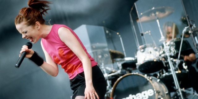 Shirley Manson rocks out on stage in a pink tank top and their hair pulled back into a ponytail.
