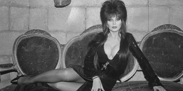 Elvira, who came out as gay in her new memoir, in a black and white photo from 1987, in a low cut black dress and laying down to the side.