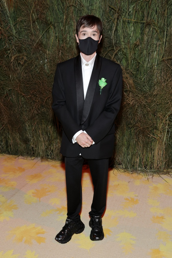 Elliott Page in a black tux and a green ribbon on his lapel, he is wearing a mask.