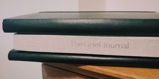 three stacked journals: the top and bottom journals are black and the middle journal is grey with the words The Grief Journal on the spine