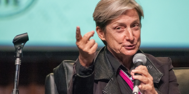 Judith Butler talks into a microphone against a blue background, they are wearing a pink tie.