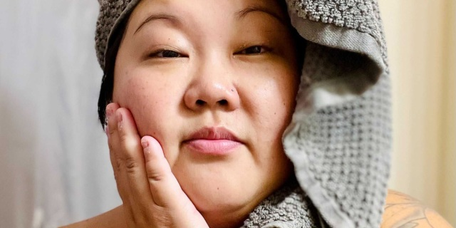 A femme Asian woman in her 30s is fresh faced from the shower and has a towel wrapped around her face.