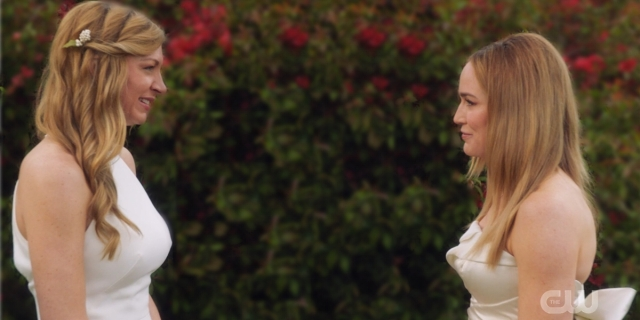 Ava and Sara stand in their wedding outfits smiling at each other.