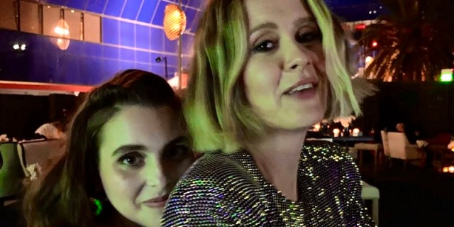 In the middle of a dark club, Beanie Feldstein hugs Sarah Paulson from behind while Sarah looks seductively into the camera.