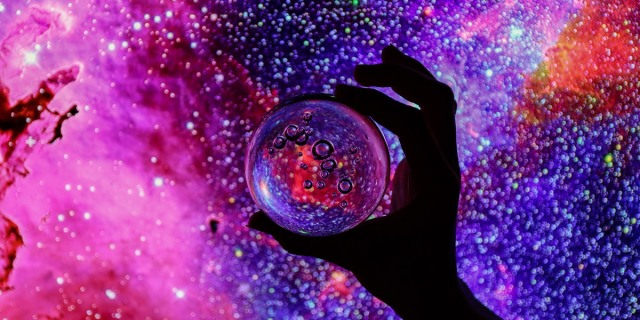 A hand that is backlit holds a magnifying glass up against a galaxy that is lit up in bisexual lighting.