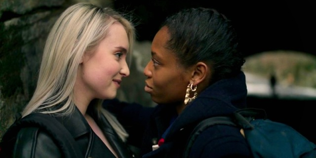 Two teenage girls, one white, Nicole, and one black, Jukebox, stare longingly at each other in a close up of their side profiles in a park in New York City.