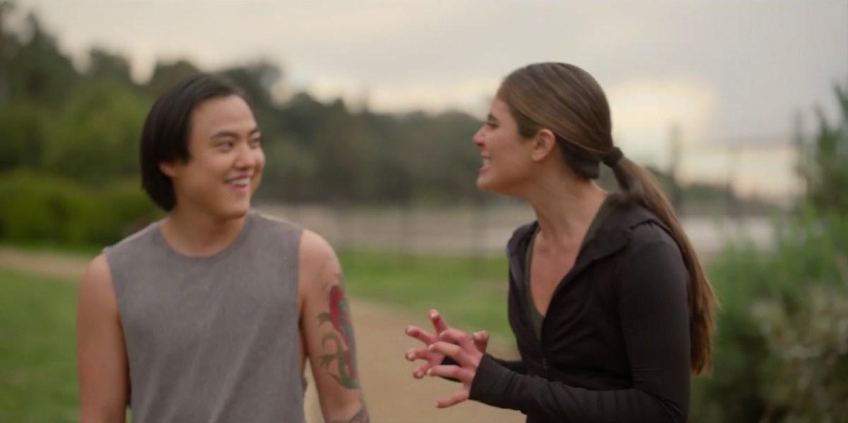 Dani making a hand gesture towards Micah, outside running