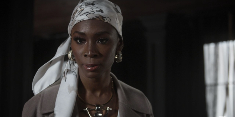 Angelica Ross looks serious with a white headwrap, chunky white earrings, and a tan jacket