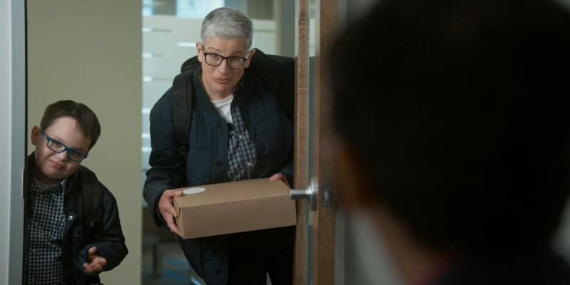 Abby stands in the doorway of an office with her nephew Mattie. She's holding a cake. They both wear glasses.