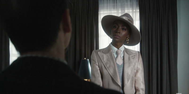 Angelica Ross is wearing a tan three-piece suit and a tan hat.
